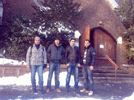 Vier Irakese vluchtelingen poseren bij de ingang van de Sacramentskerk