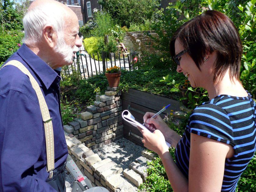 De, met een rollator door de tuin struinende bezoeker, beantwoordt een paar vragen voor de Posthoornjournaliste. Foto door Oenkenstein.