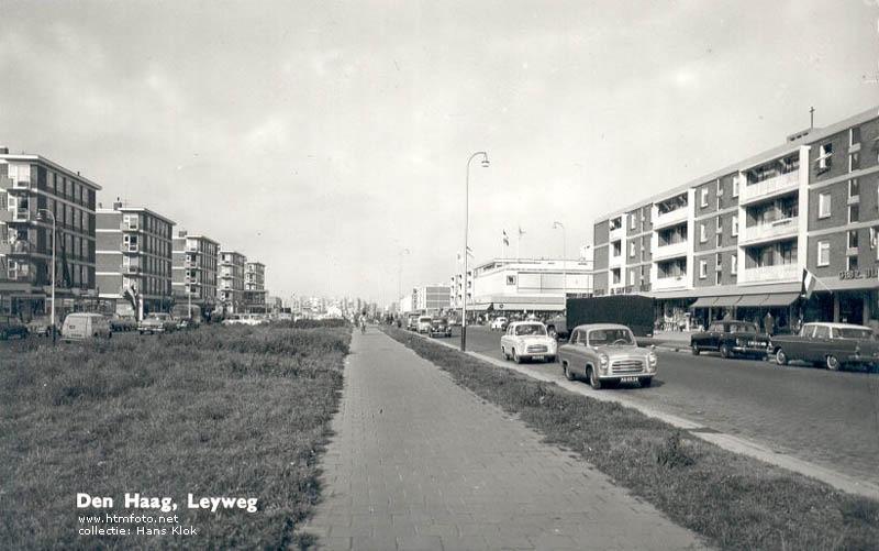 Foto: de Leyweg in de '60er jaren. Het witte gebouw met de vlaggen is van V&D. De Gruyter zat iets links van de zwarte auto op de foto. Albert Heijn net buiten beeld, rechts. In de jaren '80 is de Leyweg verbouwd. Afgesloten voor doorgaand verkeer. De groenstrook op de foto, het fietspad en het wegdek zijn volgebouwd met winkels.