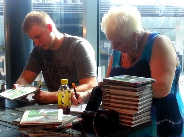 Marjon van der Vegt signeert een bundel, foto: Haagspraak